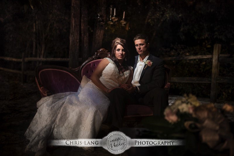 A Wedding Picture Of Newlyweds On Counch Outside At Night Lit By Chandelier