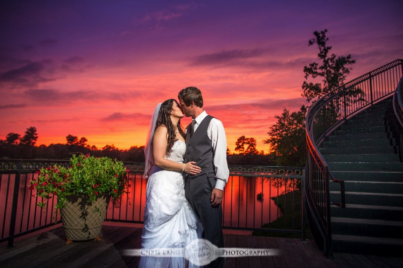 A wedding picture of a couple kissing in front if a majestic sunset with orange and red skies.  Wilmington NC Wedding Photography