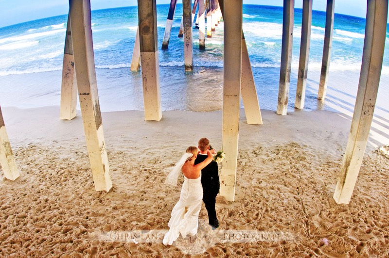 Wedding picture of a couple under a pier at Wrightsville Beach looking out to the Atlantic Ocean. Beach wedding photography
